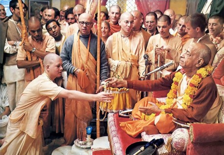 Srila Prabhupada hands sanctified beads to a new initiate. 1975.