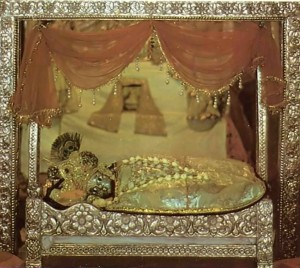 Taking rest in the Mirror Temple, little Deity of Krishna lies on soft bedding. Vrindavan 1975.