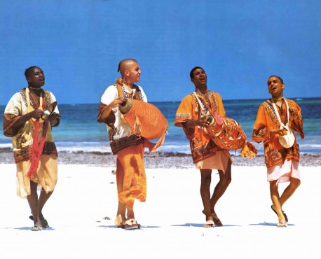 Pioneers of the Krishna consciousness movement in Africa chant Hare Krishna on the beach at Mombasa, Kenya. 1974.