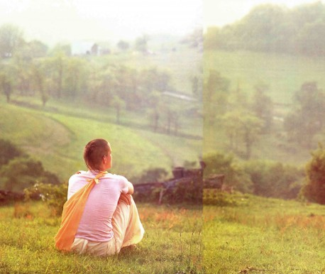 Hare Krishna Devotee sits on hill and looks at green fields. 1976.