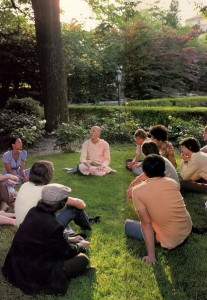 Jayadvaita dasa preaches to a group of students sitting on grass at a US college campus. 1976.