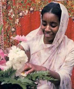 ISKCON devotee makes flower arrangements for offering to the Deities at Hare Krishna Temple. 1976.