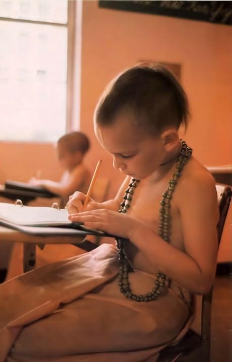 ISKCON Gurukula boy student writing in notebook. 1976.