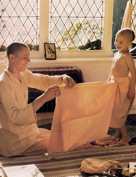 ISKCON Gurukula teacher helping boy student to put on his dhoti. 1976.