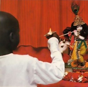Boy offers aroti to Radha Krishna Deities at ISKCON Gurukula 1976.