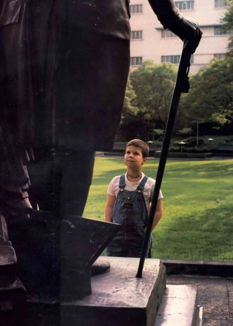 Heros: Boy looking up at statue in park