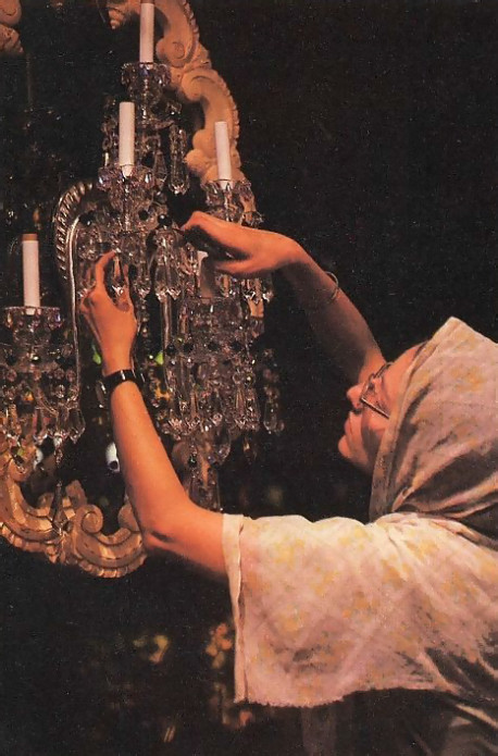 A crystal sconce gets finishing touches from Isani-devi dasi , who designed forty sconces and chandeliers for the Palace.