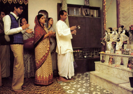 Worshiping Lord Krsna at home, Samika Rsi offers a fragrant camphor lamp as his wife. his brother. and fellow devotees join in chanting the Hare Krsna mantra.
