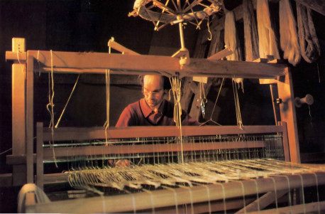 Immersed in working his loom, Bhakta Claude, a devotee artisan at the Krsna conscious farm in Valencay, France. prepares cloth from hand· spun wool.