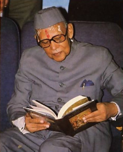 Gov. Chandreswar Singh looks through one of the books of the Krsna consciousness movement.