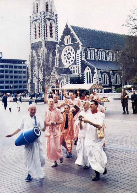 "Famous Cathedral Square in Christchurch, New Zealand, provides an appropriate site for Hare Krsna devotees to chant the holy names of God. To passersby the chanting may seem like a meaningless incantation, but in reality the repetition of the Hare Krsna mantra- especially when sung in congregation-quickly brings the chanters to a joyful state of self- realization and realization of God. As the Vedic scriptures say, ""In this age there is no way to spiritual perfection other than the chanting of God's names."""