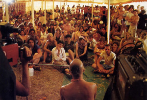 Festival-goers sit in rapt attention as Dhmadyumna Swami explains karma and reincarnation during a break between songs.