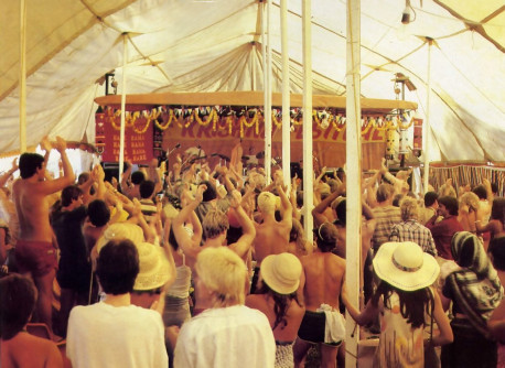 The crowd rises to its feet as the band pumps out a rhythmic rendition of the Hare Krsna mantra