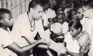 A Bengali devotee eagerly receives chippedrice-with-yogurt from His Holiness Satadhanya Swami.
