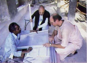 At the Srila Prabhupada memorial under construction on the temple grounds, he consults with his chief assistant, Bhaktisiddhanta dasa (wearing black shawl) and an Indian artisan.