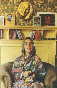 Syama-maajari-devi dasi (formerly the popular punk-rock singer-saxophonist Lora Logic) chants Hare Krsna beneath a portrait of her spiritual master, Srila Bhagavan dasa Goswami Gurudeva.