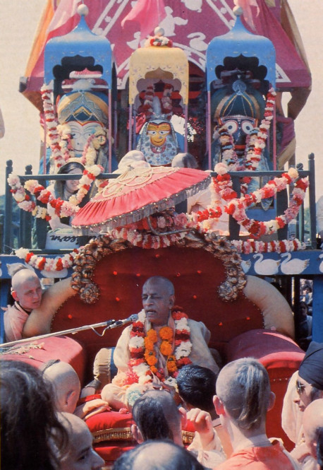 "In London in 1972, His Divine Grace A. C. Bhaktivedanta Swami Prabhupada addresses a crowd of devotees and festival-goers at the Festival of the Chariots (see article). Standing majestically above Srila Prabhupada on the towering Ratha-yatra cart are the worship able deity forms of Lord Balarama (Krsna's brother), Srimati Subhadra (Krsna's sister), and Lord Jagannatha (Krsna in His form as the ""Lord of the Universe"")."