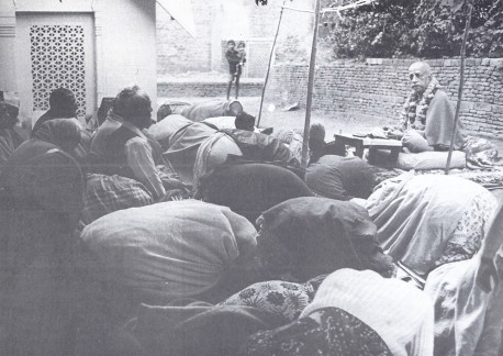 In the courtyard of Radha-Damodara: Devotees offer obeisances as Srila Prabhupada concludes chanting and begins to speak. On the left is the samadhi of Srila Rupa Gosvami.