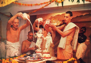 Jananivasa, Pailkajanghri , and another priest bathe Radha-Madhava with yogurt poured from conchshells.