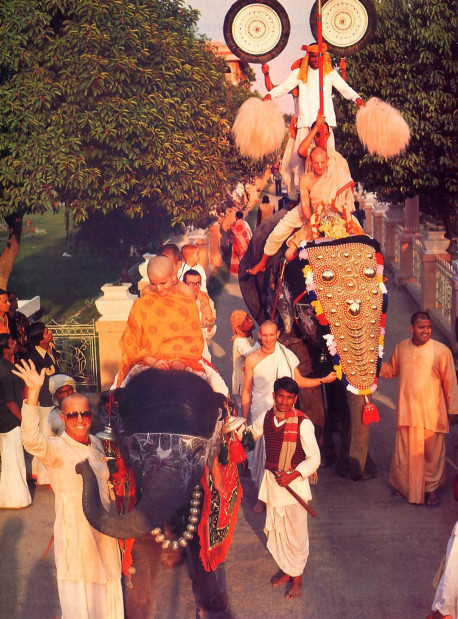 Atop an ornamented elephant, Parikajanghri steadies the Deities before him as Janannivasa leads the way in a colorful procession around the Mayapur temple gardens. A small elephant in the foreground joins Srila Bhavananda Goswami Visnupada, co-director of the Mayapur project and one of ISKCON's spiritual masters, in a wave to the camera.