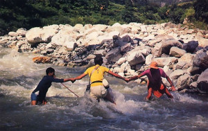 A guide helps Guru Krsna dasa and Jagatguru Swami across Ganges rapids.