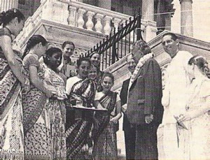 Congressman Gilman (wearing garland) is invited to sample food offered to Krsna.