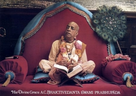 Srila Prabhupada sitting on red Vyasassana playing kartals, 1973