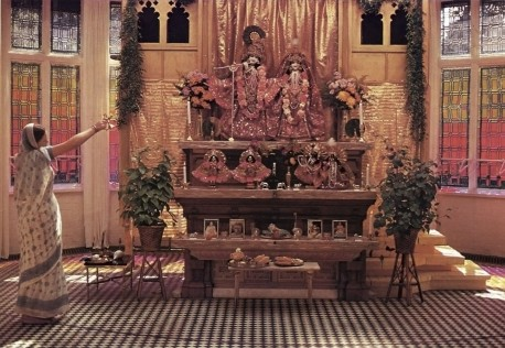 Women Hare Krishna devotee offering Aroti to the Deities Sri Sri Radha Gokulananda at Bhaktivedanta Manor Lechmore Heath Watford England 1973.