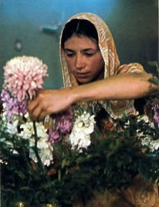 Woman Hare Krishna devotee arranging flowers for Krishna