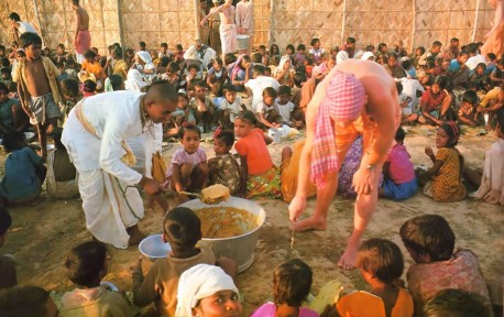 Hare Krishna devotees distributing prasadam (food) to the hungry at ISKCON Mayapur, West Bengal, India. 1974.