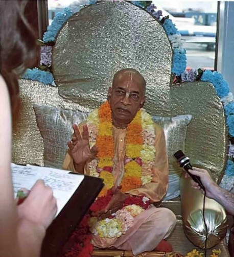Prabhupada sitting on Vyassasana in Airport speaks with press. 1975.