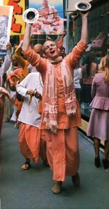 Cymbals aloft, Hare Krishna chanter leaps along Parisian thoroughfare. Paris, France. 1975.