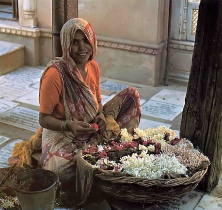 Indian Lady making flower garland to offer to Krishna. Vrindavan, India, 1975.