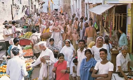 Beaming devotees chant Hare Krishna as they weave their way through one of Vrindavan's colorful bazaars. 1976.
