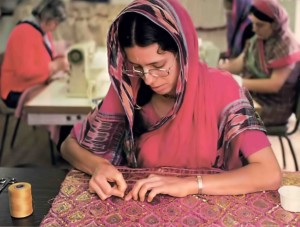 Hare Krishna devotee making clothes for Radha Krishna deities. 1976.