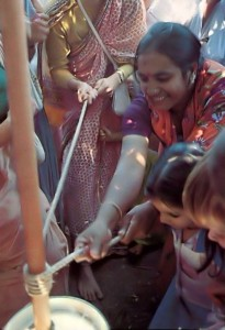 Indian Lady using butter churn at ISKCON Janmastami Festival 1976.
