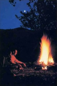 A devotee reads Bhagavad-glta by an evening fire.  France - 1977