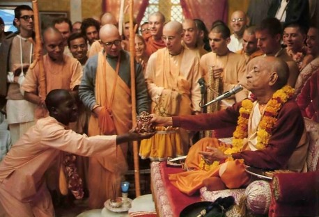 His Divine Grace A. C. Bhaktivedanta Swami Prabhupada hands a new disciple the beads upon which he will chant the Hare Krishna maha-mantra. 1977
