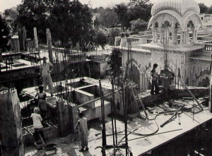 Support beams rise from the newly laid second story of the memorial shrine for Srila Prabhupada in Vrndavana, India. The dome of the Krsna-Balariima temple appears at upper right.
