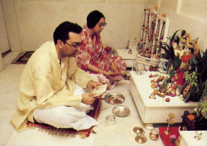 Ceremonies before the Deity of Krsna and readings from Bhagavad-gita bring Nathji and his wife Maithili to the family temple room each morning and evening. Articles for the traditional arati fill the altar: flower, conchshell, andkerchief. essential oils. incense. ghee wick lamps, and water cup.