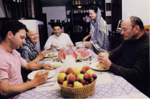 At dinner: Marco and his wife, father, and mother share sanctified food with guests.