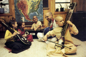Singing to glorify Krsna, Bhurijana and the children accompany themselves with traditional Indian instruments