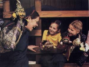 Bhurijana's wife . Jagattarani, entertains two children with her puppets .