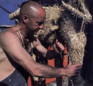A figure takes shape under the skillful hands of Bhaktisiddhanta dasa, working here in Los Angeles in 1976. To create the figure, he uses the traditional Indian method of puttala, constructing a base of straw upon which he will mold the final form in clay.