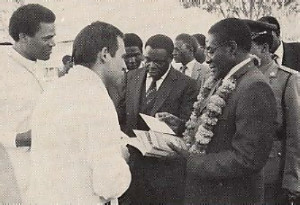 Prime Minister R . C. Mugabe (right) receives Srila Prabhupada's books from Harare temple president Devarsi dasa, as Srinatha Cakravarti dasa (far left) looks on.