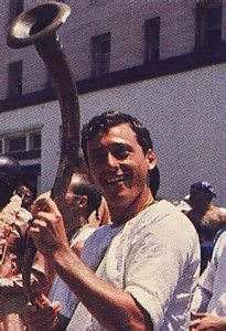 A happy celebrant gets into the spirit with as mile and blasts from an Indian horn.