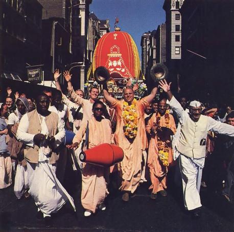 "ISKCON gurus spark New York's festival: Srila Jayapataka Swami Acaryapada, raises his famous brass ""whompers"" and dances down Fifth Avenue. At his left is Srila Gopala-Krsna Goswami Bhagavatapada."