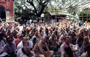 At the birthsite of Lord Caitanya, devotees listen attentively to a discourse on the Lord's mission in the material world. The tree under which Lord Caitanya took birth is in the background.