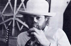 Mike Love sniffs at a rose as he listens to the conversation.