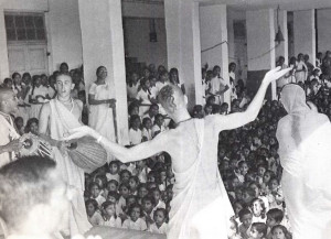 Srila Prabhupada holds lecture and chanting before a large school assembly.